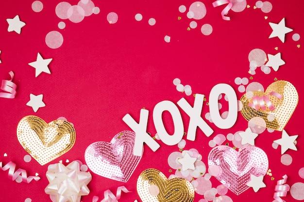 Конфетти, банты и бумажные украшения. день святого валентина или тема концепции вечеринки по случаю дня рождения. плоская планировка, вид сверху