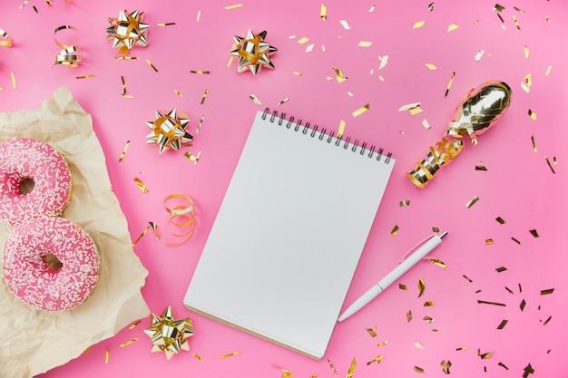 Пустая спиральная тетрадь с белой ручкой на розовой предпосылке с золотыми confetti и смычками, розовыми donuts. модный цвет и стиль. квартира лежала. копировать пространство идея блоггера.