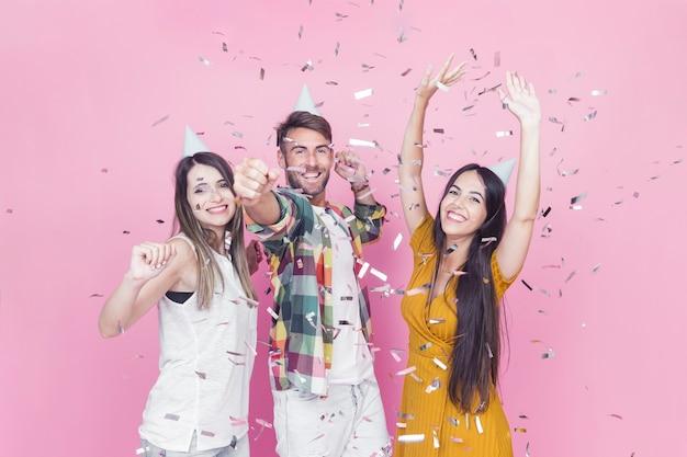 Конфетти падают на друзей, наслаждаясь розовым фоном
