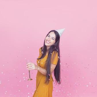 シャンパンフルートを持っている笑顔の若い女性の上に落ちる紙吹雪