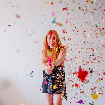 Confetti flying in air and girl behind