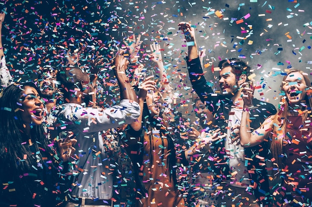 Confetti fun. group of beautiful young people throwing colorful confetti while dancing and looking happy