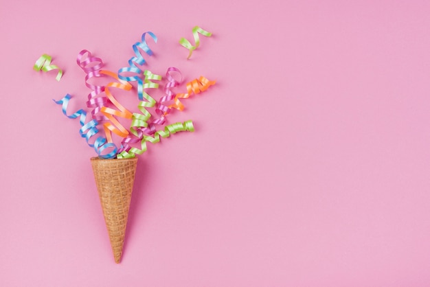 Confetti in ice-cream cone with copy-space on pink