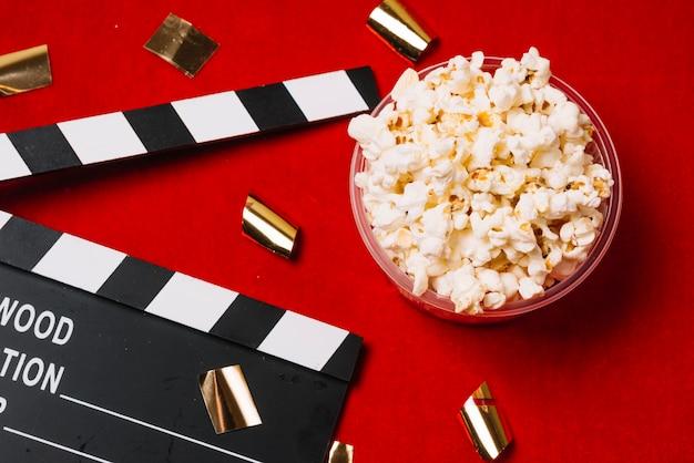 Confetti near clapperboard and popcorn