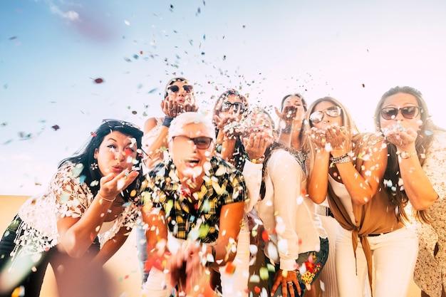 쾌활한 예쁜 숙녀를위한 카니발 또는 생일 개념-이벤트 야외를 즐기는 날아 다니는 행복한 쾌활한 미친 백인 여성을위한 색종이 파티 축하