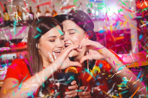 Confetti party. two young lesbian girls make a heart with their hands at a club party