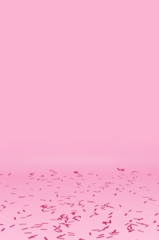 ピンクの背景に散らばった紙吹雪