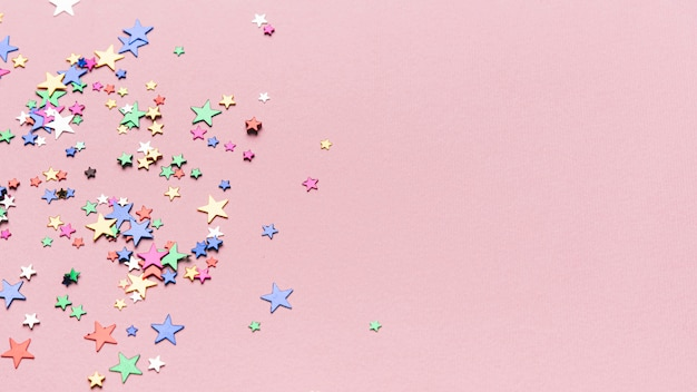 Confetti stars on pink background with copy space