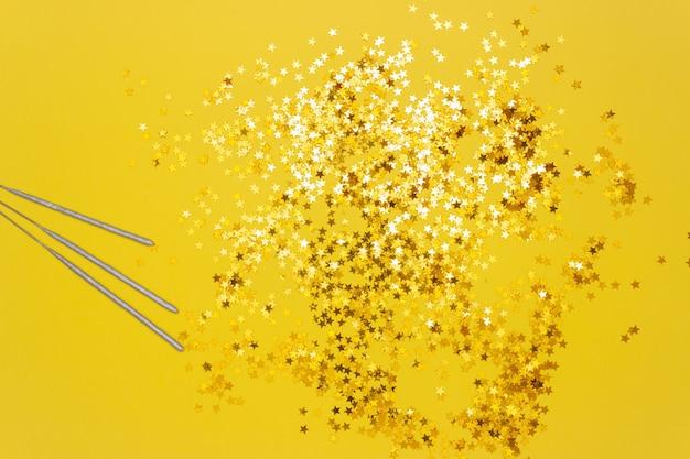 Confetti stars and sparkler sticks on yellow