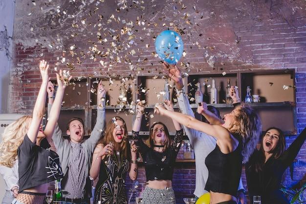Confettiと風船を持つお祝いの友人