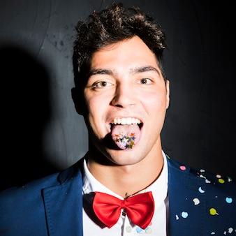 舌の上にconfettiとイブニングジャケットのハンサムな男