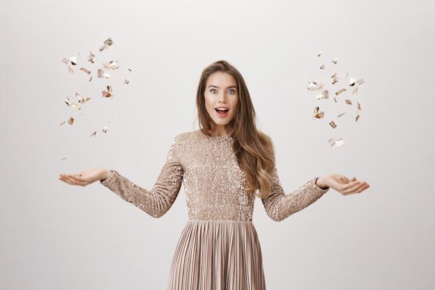 ドレスで黄金のconfettyを投げて驚いて魅力的な女性
