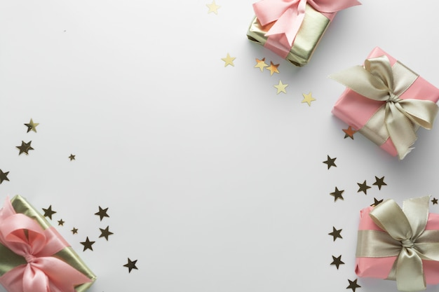 白地に美しい黄金の贈り物キラキラconffetiピンク弓リボン。クリスマス、パーティー、誕生日。シニーサプライズボックスcopyspaceを祝います。創造的なフラットレイアウトトップビュー。