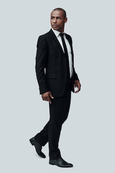 자신감과 카리스마. 회색 배경에 서서 멀리 바라보는 정장 차림의 잘생긴 젊은 아프리카 남자의 전체 길이