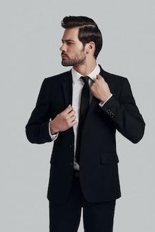 자신감과 카리스마. 정장을 입은 잘생긴 청년은 재킷을 조정하고 회색 배경에 서서 멀리 바라보고 있습니다.