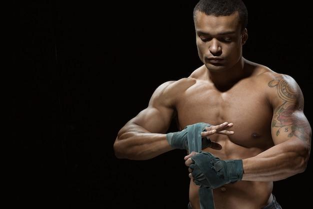 Уверенность и спокойствие. студийный снимок африканского боксера мужского пола делает повязку