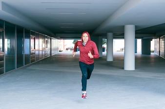 Confidence athlete man in sweatshirt hoodie running underground