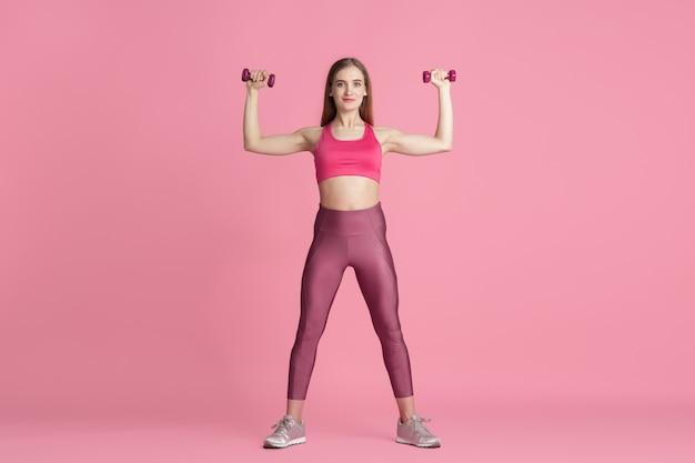 信頼。スタジオで練習している美しい若い女性アスリート、モノクロのピンクの肖像画。