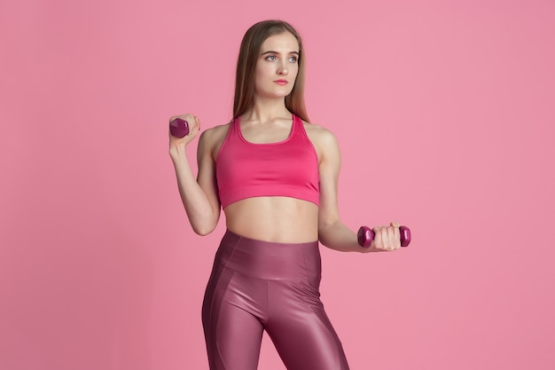 Confidence. beautiful young female athlete practicing , monochrome pink portrait. sportive fit caucasian model with weights. body building, healthy lifestyle, beauty and action concept.
