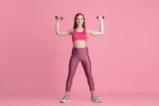 Confidence. beautiful young female athlete practicing in studio, monochrome pink portrait.