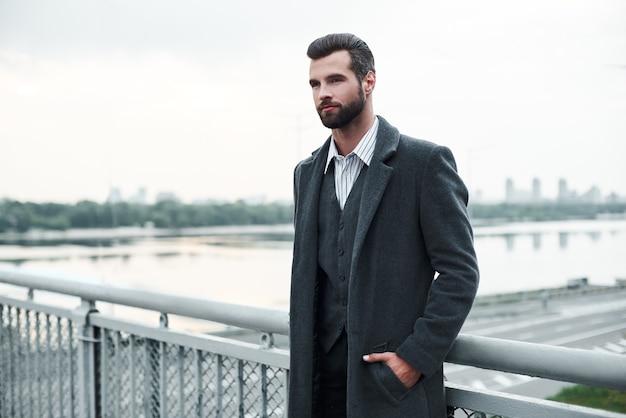 Уверенность бизнесмена, стоящего на мосту, задумчиво глядя в сторону