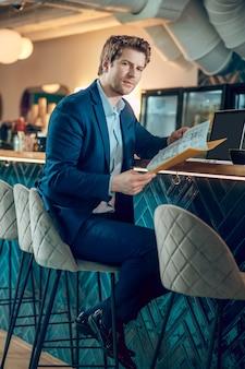 신뢰. 비즈니스 파란색 정장을 입은 자신감 있는 청년이 동료와의 만남을 기다리고 있는 카페에 앉아 문서를 살펴보고 있습니다.