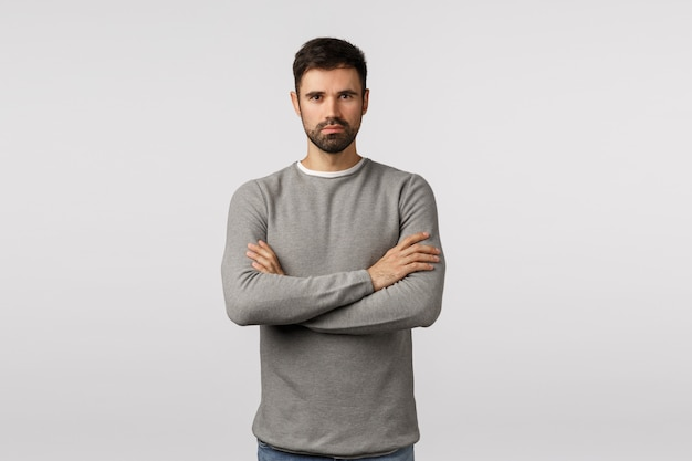 Confidence, courage and motivation concept. serious-looking handsome strong serious bearded man in grey sweater, look professional and determined, cross arms over chest, assertive ready pose