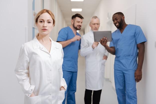 すべての決定への自信。病院で働く自信のある女性医師の笑顔とバックグラウンドでタブレットを使用している他の同僚が自信を示している