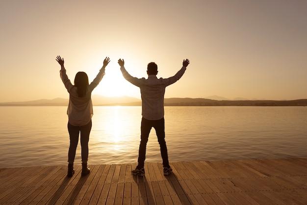 光の反射で海の海の水に昇る明るい太陽と前方の地平線を見ている開いた腕を持つ若いカップルの後ろのシルエットからの将来のビューへの自信。精神的な概念