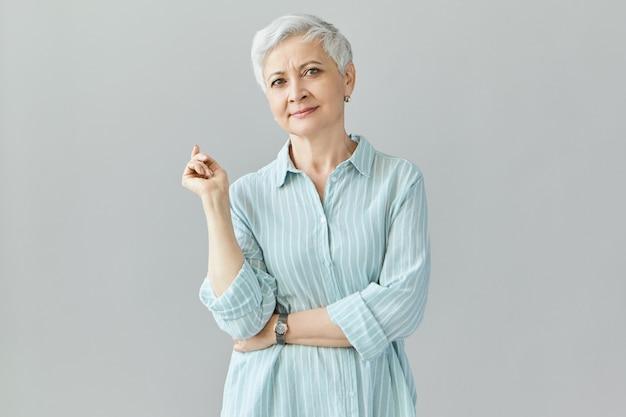 自信、人、成功、キャリアコンセプト。自信を持って笑顔で、スタイリッシュな青いシャツを着て、人差し指でジェスチャーをする60代の女性プロ