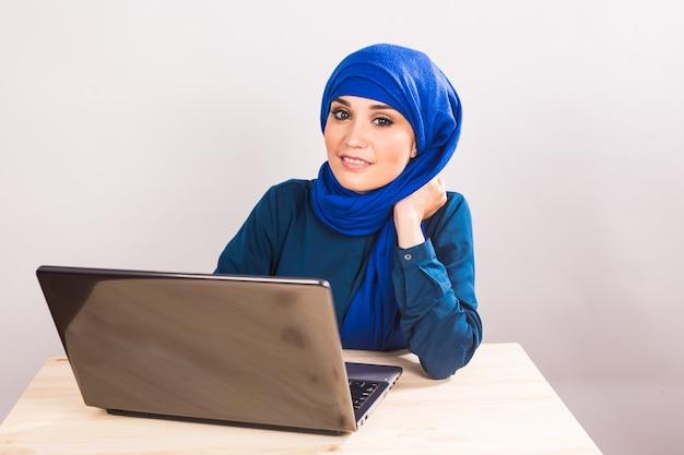 Довольно мусульманская женщина работает на ноутбуке.