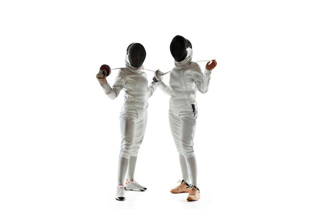 자신. 흰색 바탕에 손에 칼으로 의상을 펜싱에 십 대 소녀. 젊은 여성 모델 연습 및 운동, 행동 훈련. copyspace.