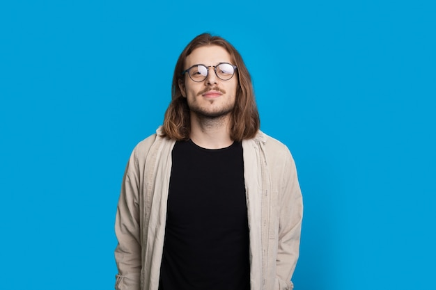 Confidend long haired man with beard is looking at camera wearing glasses and shirt on a blue studio wall