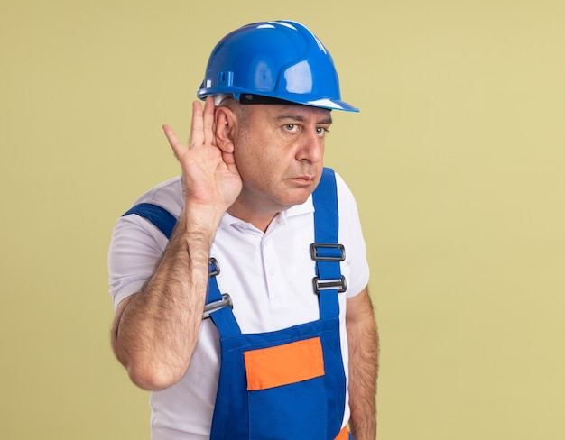 유니폼에 자신감이 성인 작성기 남자는 올리브 녹색 벽에 고립 된 귀 뒤에 손을 보유