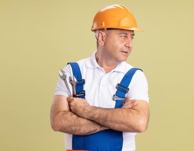 Fiducioso uomo costruttore adulto sta con le braccia incrociate guardando il lato isolato sulla parete verde oliva