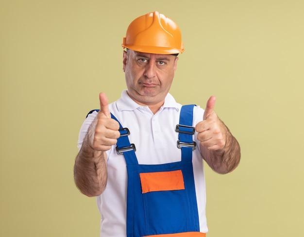 Fiducioso uomo costruttore adulto pollice in su di due mani isolate sulla parete verde oliva