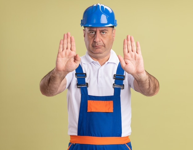 Fiducioso uomo adulto costruttore in gesti uniformi stop mano segno con due mani isolate sulla parete verde oliva
