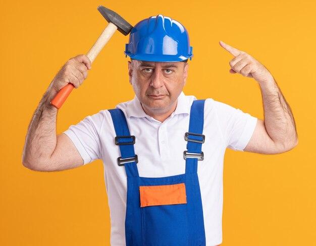 L'uomo adulto fiducioso del costruttore in uniforme tiene il martello e indica in alto isolato sulla parete arancione