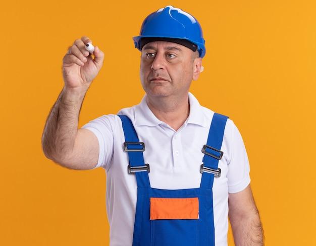 Fiducioso uomo adulto costruttore in uniforme tiene e guarda il marcatore isolato sulla parete arancione
