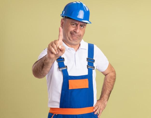 L'uomo adulto sicuro del costruttore in uniforme mostra il dito indice su verde oliva