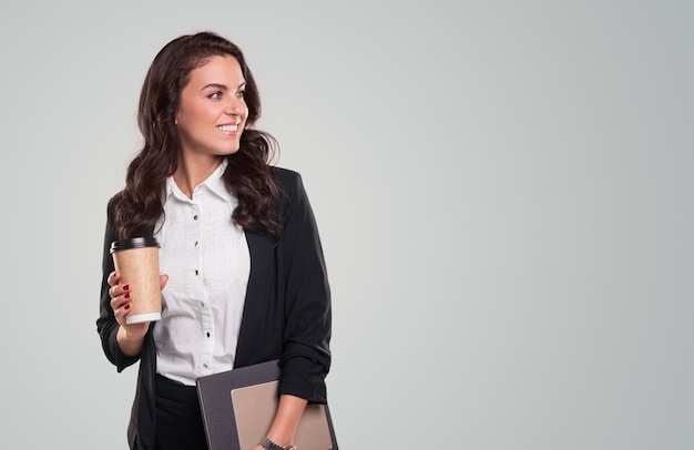 持ち帰り用のコーヒーとクリップボードのカップと笑顔と目をそらしているドキュメントとフォーマルな服を着た自信のある大人のビジネスレディ