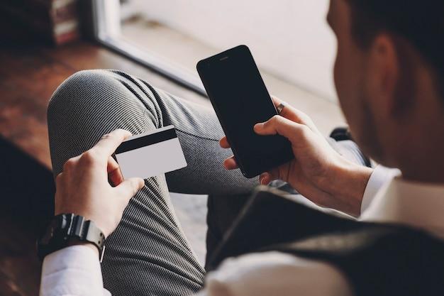 Уверенно взрослый бизнесмен сидит в кресле в своей компании возле окна, делая денежную транзакцию с помощью карты на смартфоне.