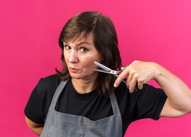 Confident adult caucasian female barber in uniform holding scissors isolated on pink background with copy space