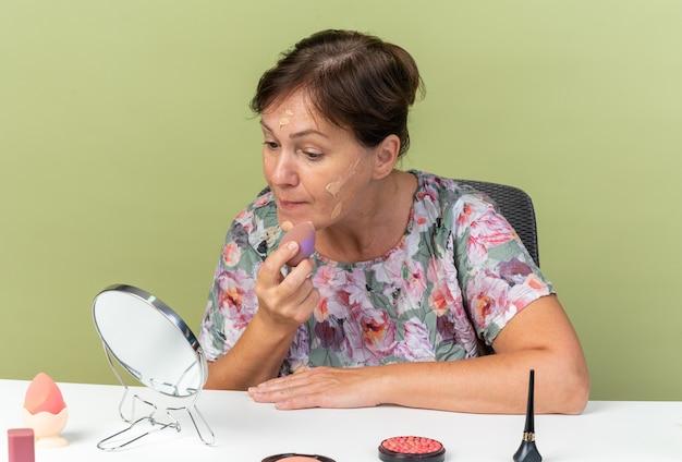 コピースペースとオリーブグリーンの壁に分離されたスポンジとトーンクリームを適用する化粧ツールでテーブルに座っている自信を持って大人の白人女性