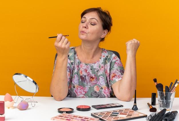Fiduciosa donna caucasica adulta seduta al tavolo con strumenti per il trucco che tengono e guardano il pennello per il trucco isolato sulla parete arancione con spazio di copia