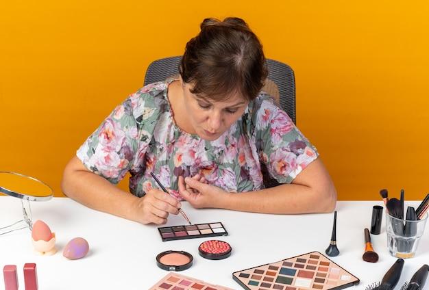 Fiduciosa donna caucasica adulta seduta al tavolo con strumenti per il trucco tenendo il pennello per il trucco e guardando la tavolozza dell'ombretto isolata sulla parete arancione con spazio di copia