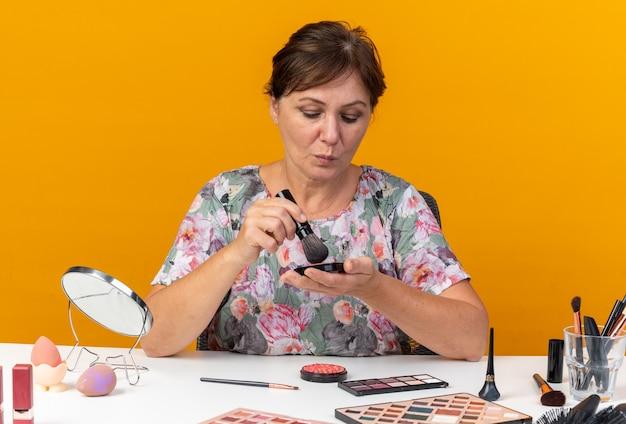 La donna caucasica adulta sicura che si siede al tavolo con gli strumenti per il trucco tiene il pennello per il trucco e guarda il rossore isolato sulla parete arancione con lo spazio della copia