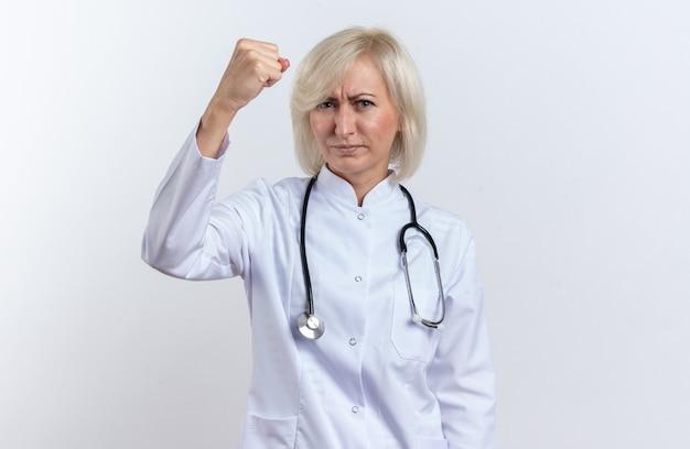 청진기가 있는 의료 가운을 입은 자신감 있는 성인 여성 의사는 복사 공간이 있는 흰 벽에 주먹을 쥐고 있다