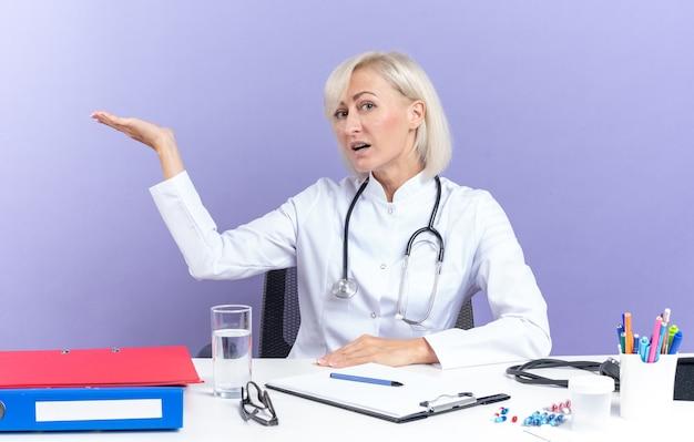의료 가운을 입은 자신감 있는 성인 여성 의사는 사무실 도구를 들고 책상에 앉아 복사 공간이 있는 보라색 벽에 격리되어 있습니다.