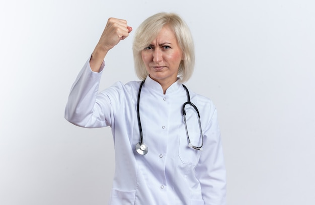 Fiducioso dottoressa adulta in veste medica con stetoscopio che tiene il pugno alzato isolato sul muro bianco con spazio copia